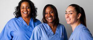 three women in healthcare uniforms smiling